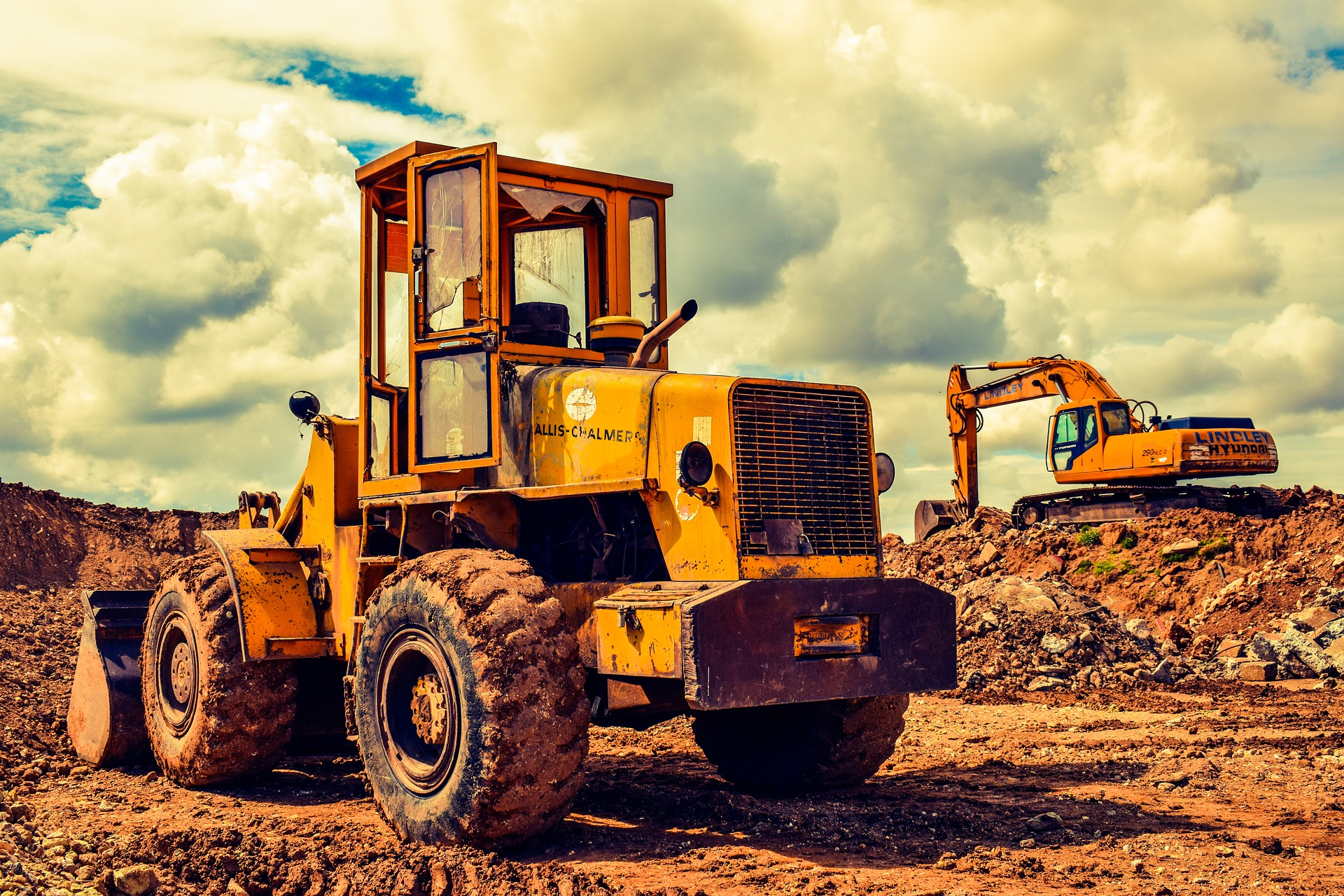Heavy equipment in the dirt with clouds in the background